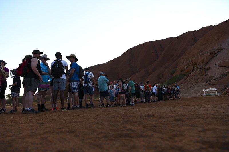 Tourists line up to climb Uluru, Australia's iconic sandstone formation, in Uluru-Kata Tjuta National Park in Northern Territory, Australia, on October 12, 2019. Photo by Lukas Coch/EPA-EFE