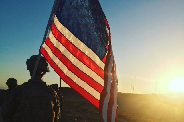 A U.S. Army soldier with the 1194th Engineer Company carries an American flag at Al Asad Air Base in Al Anbar Governorate, Iraq. File Photo by Spc. Middleton/U.S. Army National Guard/UPI