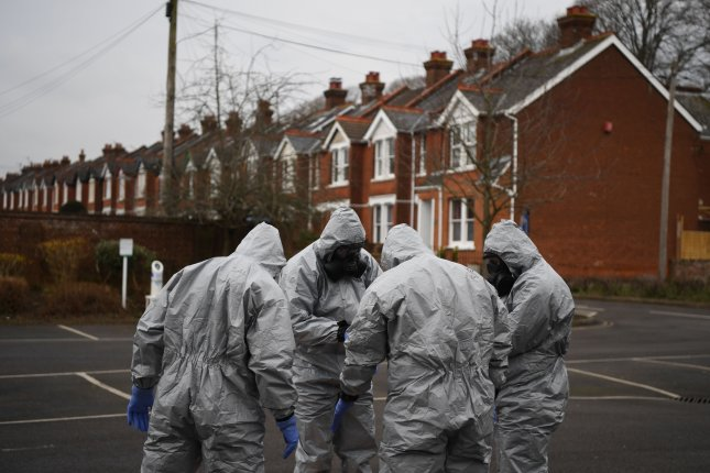 Military officers don protective clothing as they prepare to remove vehicles from a car park in Salisbury, Britain, as part of an investigation into the poisoning of a former Russian spy. Photo by Neil Hall/EPA-EFE