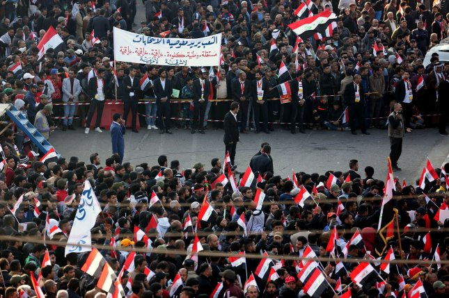 Supporters of Iraqi Shiite cleric Muqtada al-Sadr wave national flags during a demonstration at Tahrir Square in Baghdad on Saturday. Both police and protesters claimed fatalities after the protests turned violent. Photo by Ali Abbas/EPA