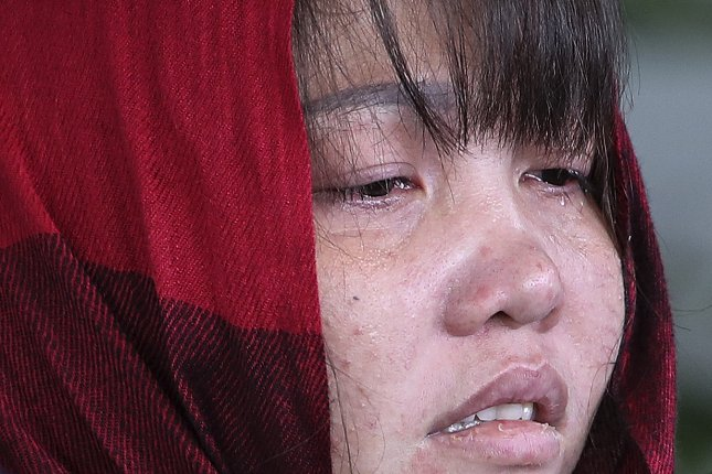 Vietnamese Doan Thi Huong cries as she is escorted by Malaysian police officers leaving the Shah Alam High Court, Shah Alam, Malaysia. Photo by Fazry Ismail/EPA-EFE