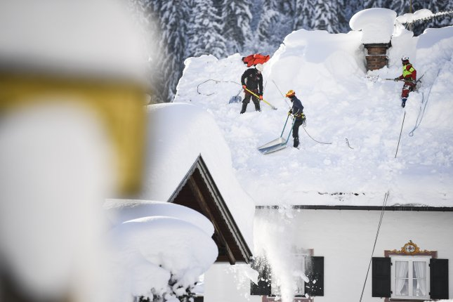 Workers clear a roof in Gerold, Germany, Friday. Austria and southern Germany have received heavy snowfalls in the past days. Photo by Philipp Guelland/EPA-EFE