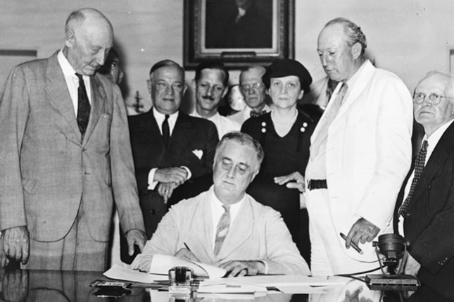 President Franklin D. Roosevelt signs the Social Security Act into Law at the White House in Washington, D.C. on August 14, 1935. Standing behind Roosevelt, left to right: Rep. Robert Doughton, man obscured behind him, Senator Robert Wagner (with folded hands), Rep. John Dingell, Sr., unidentified man with bow tie, Secretary of Labor Frances Perkins, man obscured behind her, Senator Pat Harrison (with cigar), Rep. David J. Lewis. File photo by ACME Newspictures/UPI