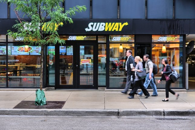 People walk past Subway sandwich store in Chicago. A judge there threw out a class-action lawsuit against the restaurant chain alleging its foot-long subs are not actually that size. Photo by Tupungato via Shutterstock