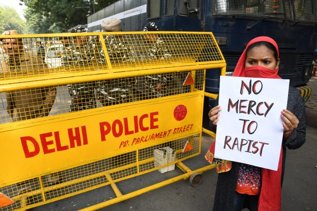 A woman holds a placard as she protests in New Delhi, India, on Saturday after a 27-year-old was raped and killed. Photo by STR/EPA-EFE