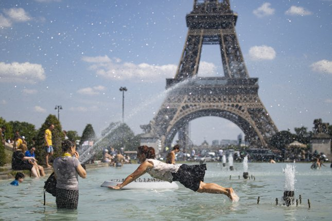 People try to cool down Tuesday in fountains across from the Eiffel Tower in Paris, France. Photo by Ian Langsdon/EPA-EFE