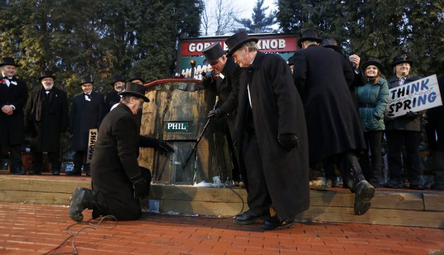 Groundhog Club co-handlers John Griffiths (R) and Ron Ploucha (L) look on as groundhog club president Bill Deeley (C) taps on the door of Punsxutawney Phil, the weather prognosticating groundhog, calling him out to make his prediction during the Groundhog Day celebration at Gobblers Knob in Punxsutawney, Pennsylvania on February 2, 2017. Phil saw his shadow and predicted six more weeks of winter. Photo by David Maxwell/EPA