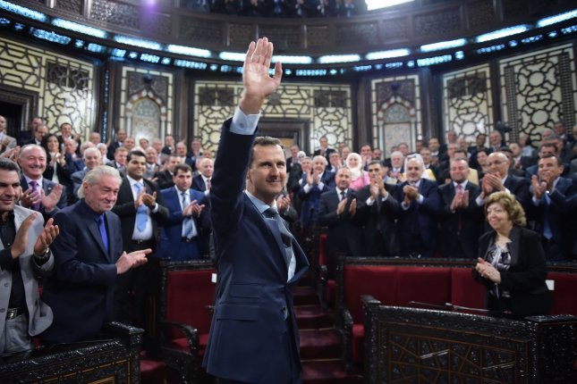 Syrian President Bashar Assad waves after speaking to the Syrian parliament in Damascus on Tuesday. During his speech, Assad stressed that we will liberate every inch of Syria from the terrorists. Photo courtesy of SANA