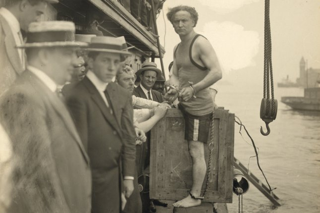 Harry Houdini stepping into a crate that will be lowered into New York Harbor as part of an escape stunt on July 7, 1912. File Photo by Library of Congress/UPI