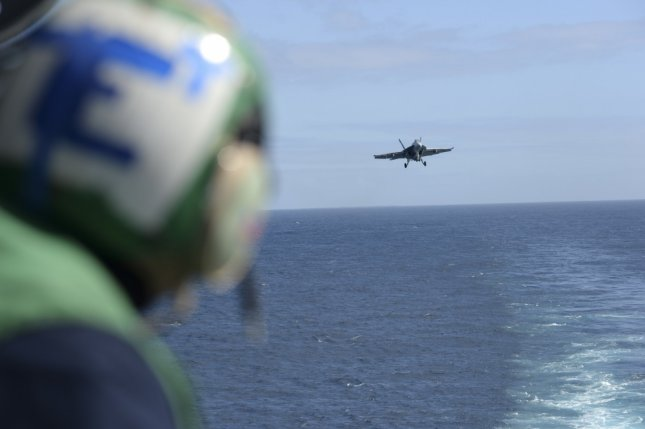 A sailor watches an F/A-18F Super Hornet, from the Flying Eagles of Strike Fighter Squadron 122, as it prepares to land on the aircraft carrier USS Nimitz on Feb. 19, 2017. On Wednesday, an F/A/-18F Super Hornet crashed near the coast of Key West, Florida. The pilot and a crew member survived. File Photo by Mass Communication Specialist Seaman Ian Kinkead/U.S. Navy