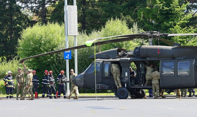 U.S. military personnel check a rotor blade on a Black Hawk helicopter that made an emergency landing in central Bucharest, Romania, on Thursday during rehearsals for a parade. Photo by Robert Ghement/EPA-EFE
