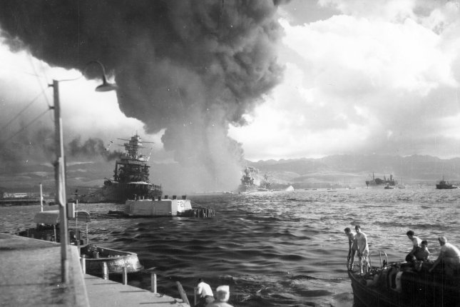 View looking down Battleship Row from Ford Island Naval Air Station, shortly after the Japanese torpedo plane attack. USS California (BB-44) is at left, listing to port after receiving two torpedo hits. In the center are USS Maryland (BB-46) with the capsized USS Oklahoma (BB-37) alongside. Most smoke is from USS Arizona (BB-39). File Photo by U.S. Navy