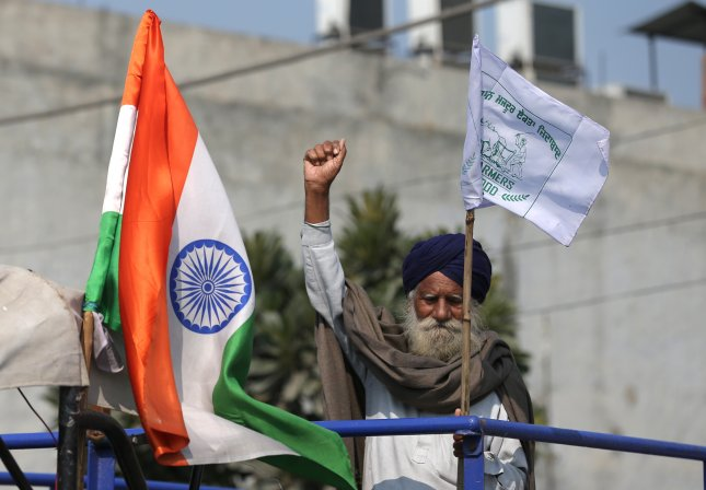 An elderly farmer raises his hand near an Indian flag displayed on a trolley as they block a highway Saturday in protest against the new agriculture laws. Photo by Raminder Pal Singh/EPA-EFE