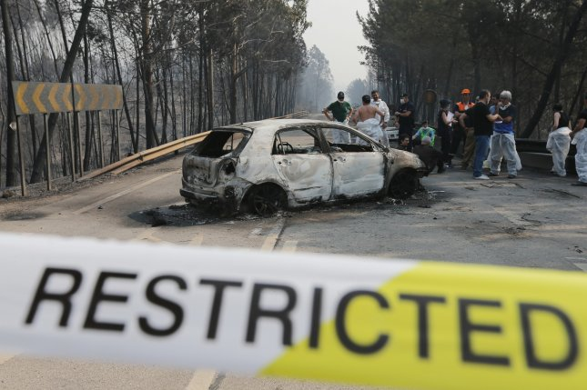 Firefighters and medical forensic investigators stand near a burnt car on the N236 road between Figueiro dos Vinhos and Castanheira de Pera, near Pedrogao Grande, in central Portugal on Sunday. At least 62 people have died in the fire, most fleeing on roads. Photo by Miguel A. Lopes/EPA
