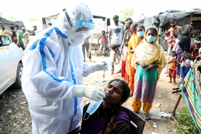 A medical staff collects a swab sample from a woman during COVID-19 tests at slum area in Jammu, India. File Photo by Jaipal Singh/EPA-EFE