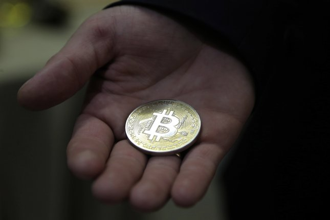 A visitor holds a Bitcoin souvenir coin at the main office of CryptoSterlingClub Alisa in Moscow in August 2017. File Photo by Maxim Shipenov/EPA-EFE