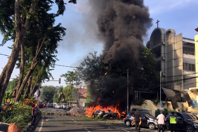 A photo made available by the government of Surabaya shows a burning vehicle shortly after a bomb blast at a church in Surabaya, East Java, Indonesia, on Sunday. Photo courtesy of Surabaya government/EPA-EFE