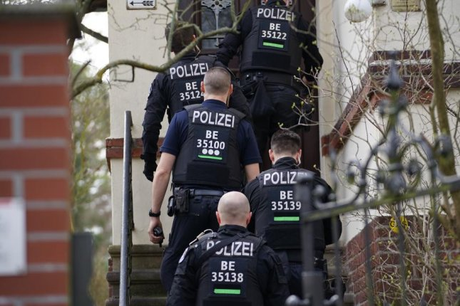 Police officers enter a house Thursday during raids in the south of Berlin, Germany. Photo by Clemens Bilan/EPA-EFE