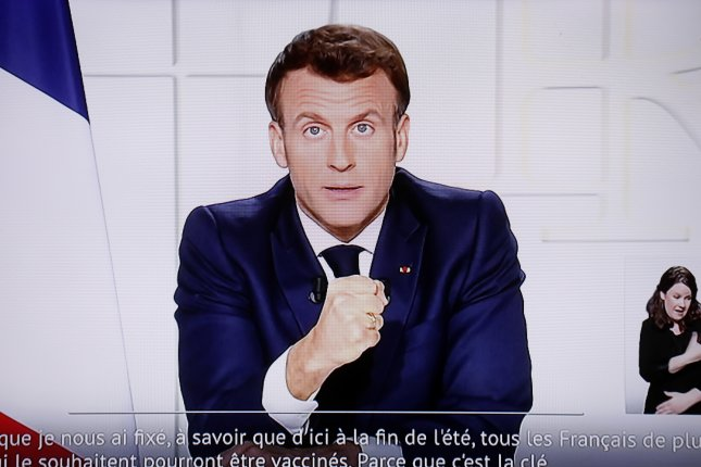French President Emmanuel Macron is seen on a screen as he makes a televised address to the nation to announce enhanced measures to fight the spread of COVID-19 on Wednesday. Photo by Sebastien Nogier/EPA-EFE