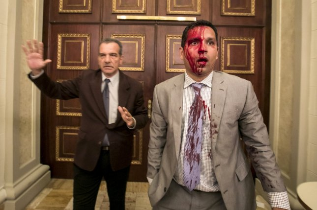 Venezuelan deputies Luis Stefanelli (L) and Jose Regnault (R) stand in a corridor of the National Assembly Wednesday after a clash with demonstrators in Caracas. A group of supporters of President Nicolas Maduro stormed the parliament on Venezuelan independence day. Photo by Miguel Gutierrez/EPA
