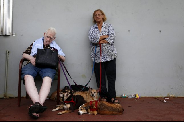 An older couple wait to be evacuated from their home by emergency personnel in the aftermath of Hurricane Maria, in Toa Baja, Puerto Rico, on Thursday. Photo by Thais Llorca/EPA-EFE