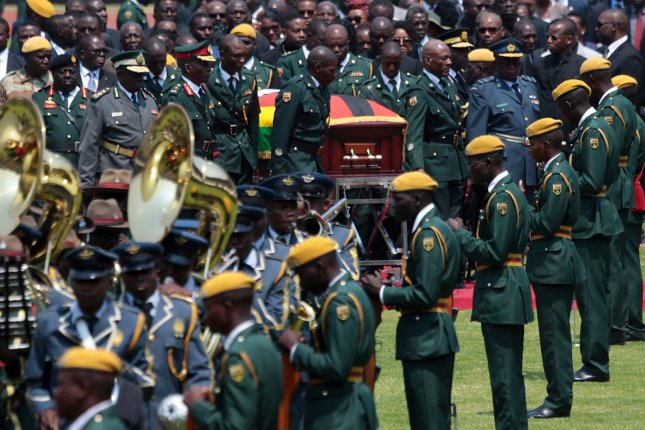 The coffin of late former Zimbabwean President Robert Mugabe is brought to the National Sports Stadium during a state funeral service, in Harare, Zimbabwe, Saturday. Photo by Aaron Ufumeli/EPA-EFE
