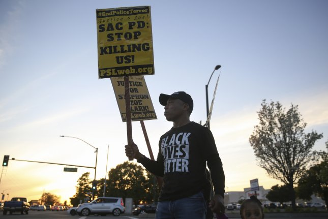 People attend a rally and vigil Saturday in Sacramento, Calif., for Stephon Clark, who was fatally shot by police. Later Saturday, a woman had minor injuries when she was struck by a Sacramento County sheriff's department SUV. Photo by Elijah Nouvelage/EPA