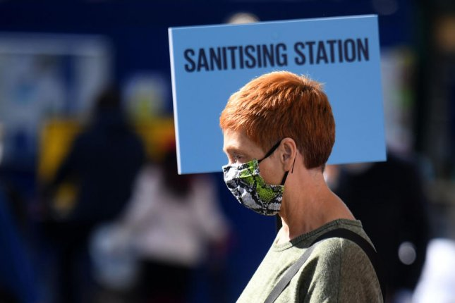 A woman passes a sanitizing station for cleaning of hands in Oxford Street in London, Britain, on Friday. Photo by Neil Hall/EPA-EFE