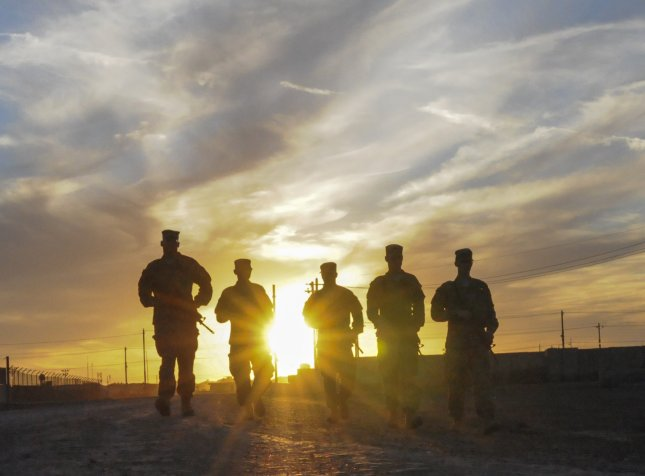 A group of U.S. soldiers walks along the road at sunset in Taji, Iraq, March 8, 2016. The soldiers are serving in Iraq as part of an international coalition that is working to destroy Daesh, also known as the Islamic State. Photo by Staff Sgt. Victor Joecks/U.S. Army National Guard/UPI