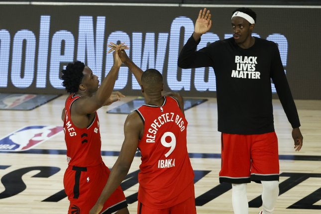Toronto Raptors forward OG Anunoby (L) is greeted by Raptors center Serge Ibaka (9) and Raptors forward Pascal Siakam (R) after a dunk during the second half of their first-round playoff game against the Brooklyn Nets on Friday at the ESPN Wide World of Sports Complex near Orlando, Fla. Photo by John G. Mabanglo/EPA-EFE