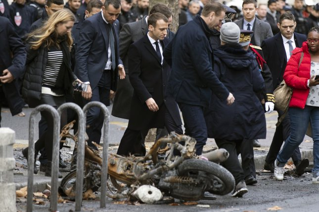 French President Emmanuel Macron (C) assesses the damages of the Yellow Vests protest a day earlier, next to the Champs Elysee in Paris on Sunday. Photo by Etienne Laurent/EPA-EFE