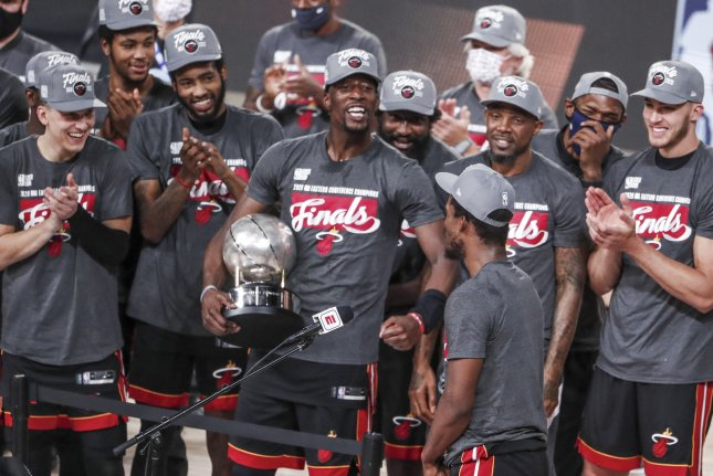 Miami Heat forward Bam Adebayo (C) holds the Eastern Conference Championship trophy as he celebrates with teammates after Game 6 of the Eastern Conference finals against the Boston Celtics on Sunday night at the ESPN Wide World of Sports Complex near Orlando, Fla. Photo by Erik S. Lesser/EPA-EFE