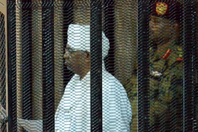 Former Sundanese President Omar Hassan al-Bashir stands in a cage during a trial in Khartoum, Sudan, on August 19, 2019. He is expected to be turned over to the International Criminal Court in the near future. File Photo by EPA-EFE