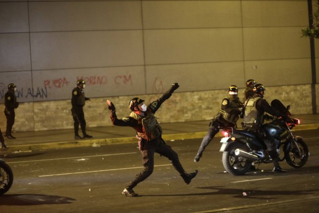A riot policeman throws an object during a protest against President Manuel Merino's transition government at San Martin Square, in Lima, Peru, on Friday. Photo by Aldair Mejia/EPA-EFE