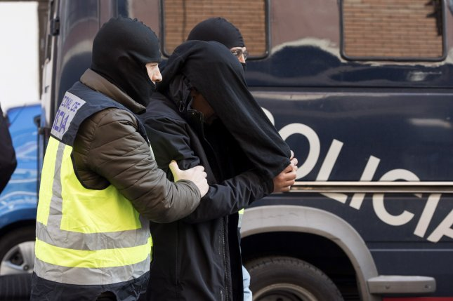 Spanish police escort a Moroccan man who has been arrested for his alleged links with the Islamic State in Vitoria, the Basque Country, northern Spain, last month. Photo by Adrian Ruiz de Hierro/EPA