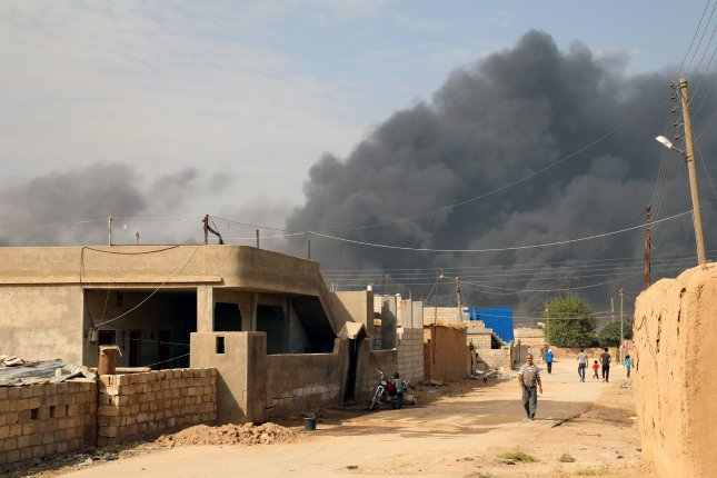 Smoke clouds rise from the scene of clashes near Ras al-Ayn, northeastern of Syria on Thursday, before cease-fire between Turkey and Kurdish militants. Despite the cease-fire, both sides said there has been fighting in the town. Photo by Ahmed Mardnli/EPA-EFE