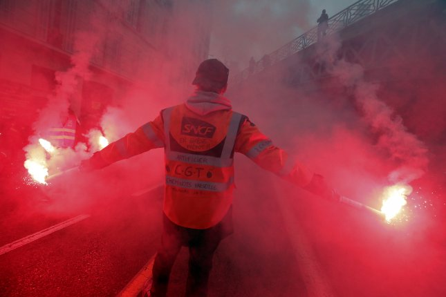 A man wearing a jacket of the French National Railway Company SNCF holds flares during a mass demonstration Friday in Marseille, France. Photo by Sebastien Nogier/EPA-EFE