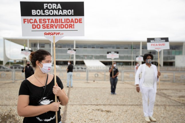 Federal public officials wear masks at protest against Brazil's President Jair Bolsonaro in front of the Palacio Planalto headquarters in Brasilia. File Photo by Joedson Alves/EPA-EFE
