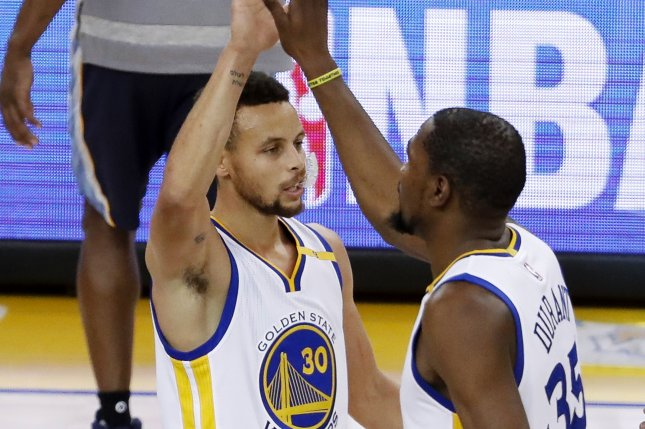 Golden State Warriors forward Kevin Durant (R) is greeted by Golden State Warriors guard Stephen Curry (L) after Durant scored a three-point jumper against the Memphis Grizzlies. File photo by John G. Mabanglo/EPA