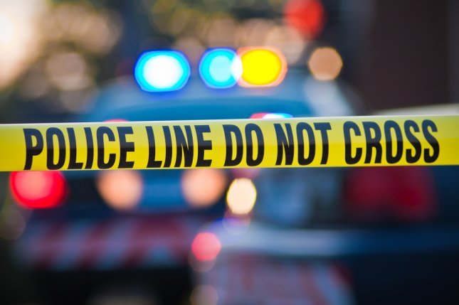A crime scene is pictured with yellow law enforcement line with police car and lights in the background. Carl Ballou/Shutterstock
