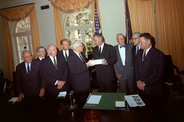Members of the Warren Commission present their report on the assassination of President John F. Kennedy to President Lyndon B. Johnson. From L-R: John McCloy, J. Lee Rankin (General Counsel), Senator Richard Russell, Representative Gerald Ford, Chief Justice Earl Warren, President Lyndon B. Johnson, Allen Dulles, Senator John Sherman Cooper, and Representative Hale Boggs. On November 29, 1963, Johnson appointed the Warren Commission to investigate the assassination of President John Kennedy. File Photo by LBJ Library/UPI