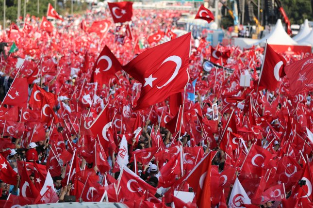 Citizens hold Turkish flags during a celebration in Istanbul, Turkey. New figures Monday showed the country has entered its first recession in nine years. File Photo by Tolga Bozoglu/EPA-EFE