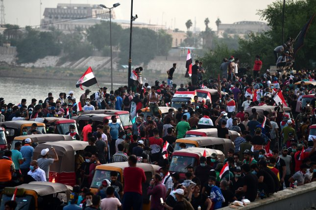 Iraqi protesters gather over the Al-Jumhuriya Bridge that leads to the headquarters of the Iraqi government inside the high-security Green Zone area in Baghdad on Saturday. Photo by Murtaja Lateef/EPA-EFE