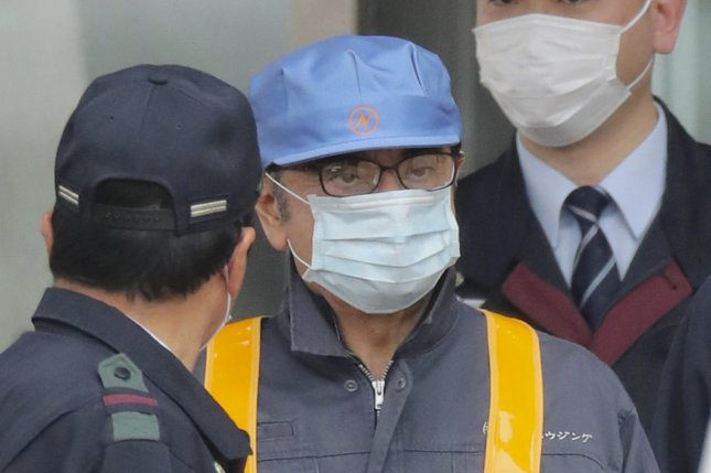 Carlos Ghosn, in a mask, blue cap and gray jumpsuit, leaves a Tokyo, Japan, jail Wednesday after posting bail. Photo by Jiji Press Japan/EPA-EFE