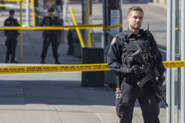A Toronto police officer stands on Yonge Street in northern Toronto, Canada, Monday after several people were killed when a van ran into a crowd of pedestrians. Photo by Warren Toda/EPA-EFE