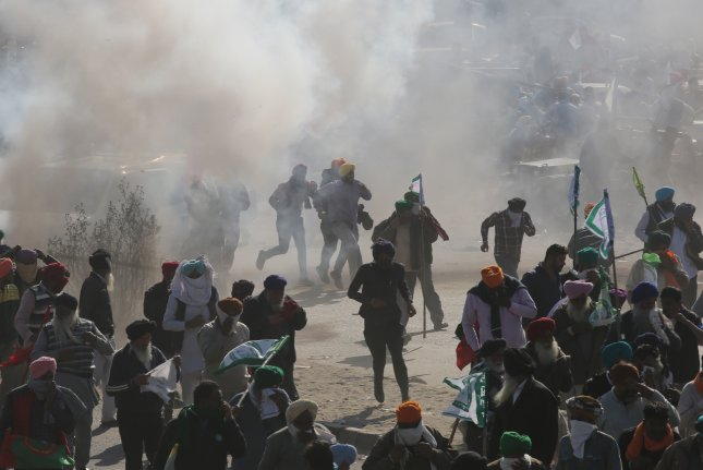 A tear gas shell fired by police explodes near protesting farmers in India after police try to stop farmers from entering Delhi to protest against new farm laws, at the New Delhi, Haryana Sindhu border on Friday. Photo by Rajat Gupta/EPA-EFE
