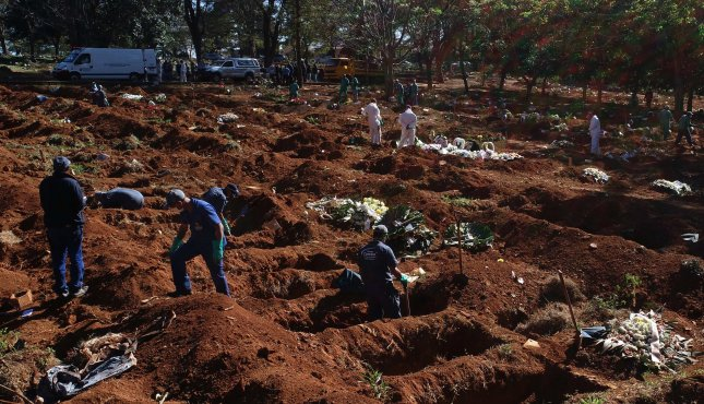 Workers burying victims of the COVID-19 pandemic in the Vila Formosa cemetery, the largest in Latin America, in Sao Paulo, Brazil, on Tuesday. Photo by Paulo Whitaker/EPA-EFE