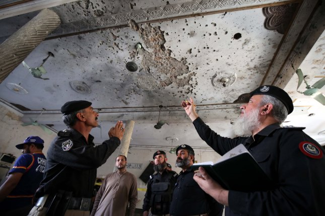 Security officials inspect damage at an Islamic seminary in Peshawar, Pakistan, on Tuesday after a bombing attack that killed several adult students. Photo by Bilawal Arbab/EPA-EFE