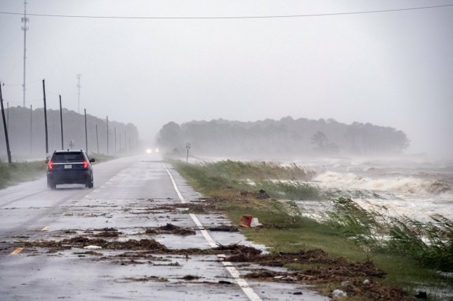 A car drives by crashing waves as Hurric/DAN ANDERSOane Sally approaches in Alabama Port, Ala., in September 2020. Residents of Central and Southern states should keep a close eye on violent conditions. Photo by Dan Anderson