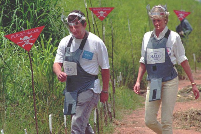 Britain's Princess Diana, dressed in a heavy-duty protection vest and face shield, walks with a mine- clearing expert in the high plateau near Huambo, Angola, on January 15, 1997. File Photo by Antonio Cotrim/EPA-EFE